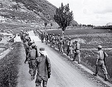 Lines of troops marching along a road