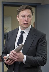Musk, dressed in a suit, holds a metal model of the sleek Starship