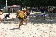 Two teams of players, one in yellow the other in blue, play a form of rugby on a sunlit beach; the central yellow player runs forward, towards the right of picture, clutching the ball with one hand, close to his chest.