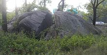 A photograph of a very large rock, about the size of a small truck, that has a large fissure in the middle. The rock is surrounded by trees and other vegetation.