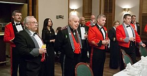 Mess jacket - Two St John Ambulance of Canada officers in mess uniform (mess dress), black jacket with grey facings and cuffs, and red vest; with others in Canadian army mess uniforms.