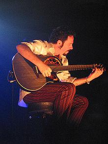 Lukather sidas sur scenejo, prilumita per lumĵetilo, ludante malhelgrizan Ovation Adamas-akustik-elektran gitaron.