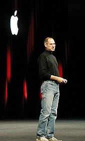 Full-length portrait of man about 50 years old wearing jeans and a black turtleneck shirt, standing in front of a dark curtain with a white Apple logo
