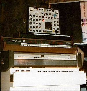 EMS Synthi A - EMS SynthiA (top) as used on stage by a progressive rock band; underneath are an EMS DK keyboard controller, Solina String Ensemble, Optigan, and an M400 Mellotron