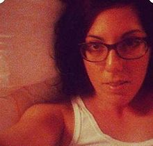Tehila Hakimi headshot - a slightly fuzzy image of Tehila Hakimi, from the shoulders up. She is wear a white tank top. She has dark hair, shoulder-length, and is wearing glasses.