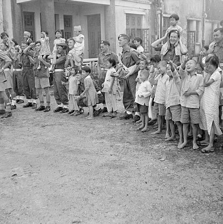 The British Reoccupation of Hong Kong in 1945: Men of 42 Marine Commando and children from the Tai Po Orphanage watch a fireworks display during a party hosted by the unit.