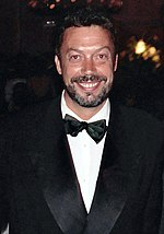 Tim Curry, a Caucasian man with a beard and short brown hair facing the viewer and smiling. He is wearing a Tuxedo.