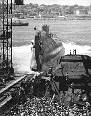 From an inclined launching slipway, Triton slides into the water, creating a large disturbance.