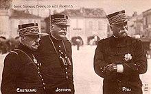 Fotografia monocromática de um grupo de três homens em trajes gerais, usando bonés.