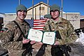 U.S. Army Cpl. Joshua Power, right, assigned to Bravo Troop, 3rd Squadron, 71st Cavalry Regiment, 10th Mountain Division, holds an honorable discharge certificate during a re-enlistment ceremony at Forward 140102-A-RU942-057.jpg