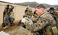 U.S. Marine Corps Lance Cpl. Tarri Smith and fellow Marines, assigned to Fleet Antiterrorism Security Team Company Pacific, 2nd Platoon, put on gas masks while simulating a chemical, biological, and radiological 120306-N-SD300-255.jpg