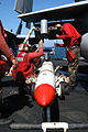 US Navy 030314-N-9593M-042 Aviation Ordnancemen prepare to hoist an Air Launched Guided Missile Eighty Eight (AGM-88) HARM missile onto a wing.jpg