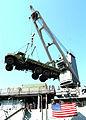 US Navy 051018-N-0716S-009 A crane aboard the dock landing ship USS Pearl Harbor (LSD 52) unloads a 7-ton heavy lift dump truck from its flight deck in Karachi, Pakistan.jpg