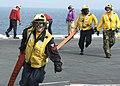 US Navy 060303-N-7318W-003 Sailors from Air Department run a fire hose to a hose team to fight a simulated aircraft fire on the flight deck aboard the Nimitz-class aircraft carrier USS Dwight D. Eisenhower (CVN 69).jpg