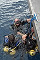 US Navy 060504-N-6775N-018 Mobile Diving and Salvage Unit One Detachment Three members stand by on the surface while waiting for the rest of their team to enter the water.jpg