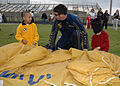 US Navy 060519-N-3342W-006 Navy Leap Frog Parachute Team member Petty Officer 1st Class Nix White teaches two young fans how to pack a parachute.jpg