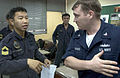 US Navy 060531-N-9851B-001 Damage control team leaders, Republic of Singapore Navy (RSN) 1st Sgt. Choon Wye Wong and Damage Controlman 3rd Class Chris Maynard discuss how they will divide participants in a combined damage contr.jpg