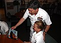 US Navy 060623-N-5367L-008 Storekeeper Seaman Angela Nice gives Master Chief Petty Officer of the Navy (MCPON) Terry Scott a signed copy of All Hands magazine in which she appeared on the cover.jpg