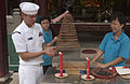 US Navy 060702-N-9851B-009 Electrician's Mate 2nd Class Jovibs Canoy, assigned to the rescue and salvage ship USS Salvor (ARS 52), lights incense for luck in Thien Hau Pagoda.jpg