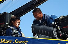 US Navy 060821-N-4729H-108 Aviation Machinist's Mate 1st Class Patrick Palma, a crew chief for the Blue Angels aerial demonstration team, helps local CBS TV reporter Anne-Marie Green prepare for her orientation flight.jpg