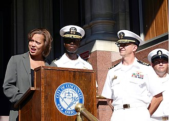 Seal of Cincinnati - Councilmember Laketa Cole and Navy officers at a ceremony in front of City Hall. The city seal is used in formal contexts, such as on lecterns.