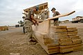 US Navy 071020-N-0553R-002 Steelworker Constructionman Recruit Keith Rodak, stationed with Naval Mobile Construction Battalion (NMCB) 1, loads wood supplies at a camp.jpg