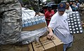 US Navy 080903-N-6266K-032 Army National Guard Spc. Jacquelyn Smith hands out bottles of water and boxes of meals ready to eat.jpg