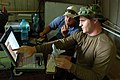 US Navy 090328-N-5242D-028 Sonar Technician (Surface) 2nd Class Dan Simmering, right, shows Tad, a Uganda-based government contractor, what he believes to be a similarity between a sonar reading and a 1-200 scale model of the I.jpg