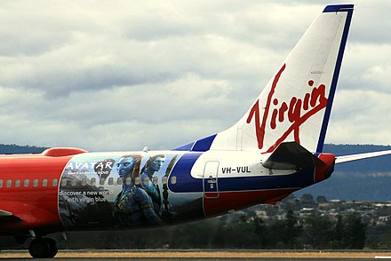 "View of aircraft aft fuselage showing advertisements against a red background. The tail contains the underlined word ""Virgin""."