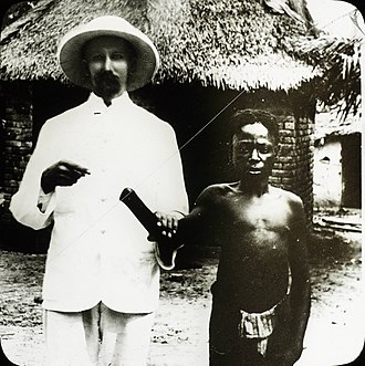 Belgian colonial empire - A white missionary posing with Congolese man, mutilated by the Congo Free State government