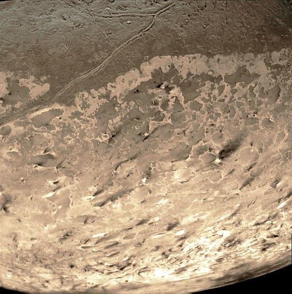 Сделанный «Вояджером-2» в 1989 году снимок Тритона. Тёмные струи — следы извержений криовулканов