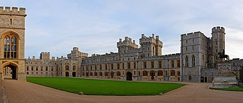 A photograph of a grey Gothic quadrangle with a green grass square in the middle. On the left, a block of the building makes up the near ground. A gatehouse is in the middle of the right hand part of the quadrangle.