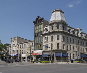 """Downtown Guelph - Intersection of Wyndham and Macdonell streets in Downtown Guelph.  The Petrie Building built in 1882 is visible (with red """"Restaurant"""" sign) ."""
