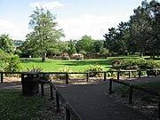 Area with grass and trees. In the distance is a children's play area and in the foreground a path with wooden rails.