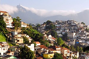 Favela - Rio's Santa Teresa neighborhood features favelas (right) contrasted with more affluent houses (left). The Christ the Redeemer, shrouded in clouds, is in the left background.
