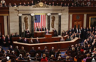 2005 State of the Union Address - President George W. Bush delivering the Address. Sitting behind Bush are Vice President Richard B. Cheney and House Speaker Dennis Hastert.