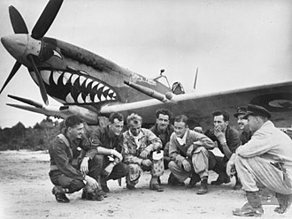 """No. 457 Squadron RAAF - Pilots of No. 457 Squadron receive final instructions for their flight back to Australia in October 1945. All of the squadron's aircraft were painted with a shark's mouth, earning it the nickname the """"Grey Nurse Squadron""""."""