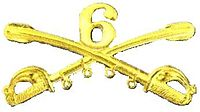 A computer generated reproduction of the insignia of the Union Army 6th Regiment cavalry branch. The insignia is displayed in gold and consists of two sheafed swords crossing over each other at a 45 degree angle pointing upwards with a Roman numeral 6