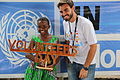 A UN VOLUNTEER IN A POSE WITHA SCHOOL GIRL BEFORE BEEN PRESENTED WITH A CARVING. (23826036565).jpg