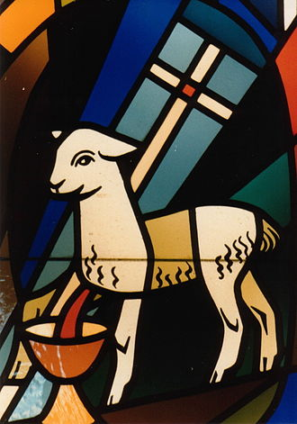 Outline of Christianity - The Lamb of God with a vexillum and chalice in stained glass, a symbol of Christ as the perfect sacrifice.