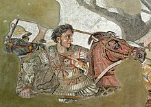 A young, clean-shaven man in heavy armour sits astride a brown horse. His breastplate bears the face of the Medusa, although his companions wear metal helms, only his short curly dark hair separates him from a deadly blow. In his right hand he grasps the shaft of a long spear, his determined face stares in sharp profile toward the right of the picture.