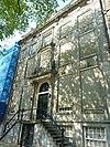 foto van Dubbel huis met zandstenen gevel met hoeklisenen, onder rechte lijst met triglyfen, consoles en attiek, gebeeldhouwde middentravee met balkon