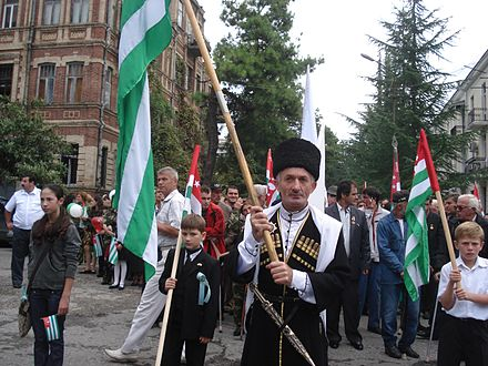 Abkhazians carrying the republic's flags in a parade. Apsua Holding Apsny Flag.jpg