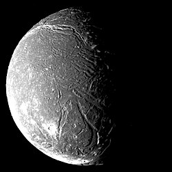the dark face of Ariel, cut by valleys and marked by craters, appears half in sunlight and half in shadow