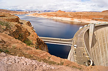 Side view of a large concrete dam impounding a lake surrounded by red-rock hills