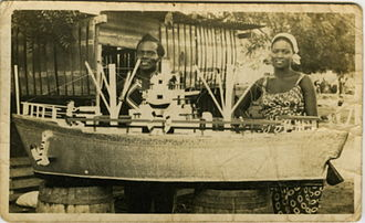 "Ga-Adangbe people - Ataa Oko and his third wife, in front of his boat coffin, about 1960. p. 137,""The buried treasures of the Ga"", 2008"