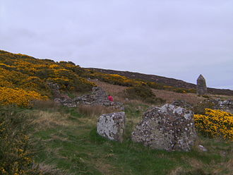 Highland Clearances - Ruins of the Badbea longhouses with the 1911 monument in the background