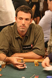 Ben Affleck holds chips while sitting at a poker table