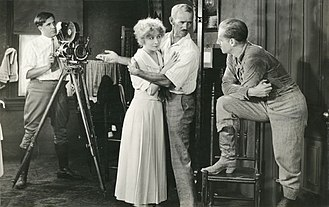 "Jack Holt (actor) - Original caption: ""Howard C. Hickman, husband and director of Bessie Barriscale, shows leading man Jack Holt how to make love to Mrs. Hickman."" This appears to be a production still from Kitty Kelly, M.D. (1919). If so, the cameraman behind the Bell & Howell model 2709 is Eugene Gaudio."