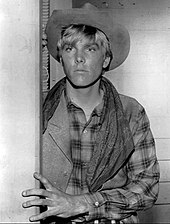 A black-and-white photo of a young Caucasian man with light-colored hair. He is wearing a cowboy hat and flannel shirt. He looks to the left of the camera, holding his left hand against the wall.